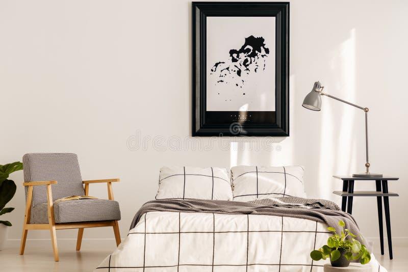 Butaca retra gris en el dormitorio blanco interior con acentos de madera imagen de archivo