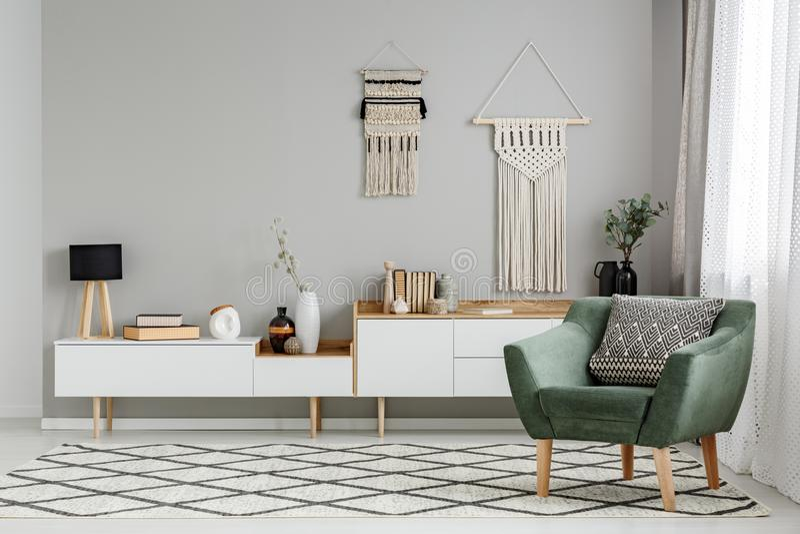 Butaca verde en la alfombra modelada en interio brillante de la sala de estar imágenes de archivo libres de regalías