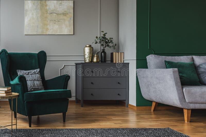 Butaca verde esmeralda con la almohada al lado de la cómoda de madera gris en interior oscuro de la sala de estar imagen de archivo