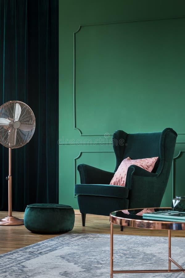 Butaca verde esmeralda del terciopelo con la almohada en colores pastel en la sala de estar de moda interior con los acentos de c fotografía de archivo