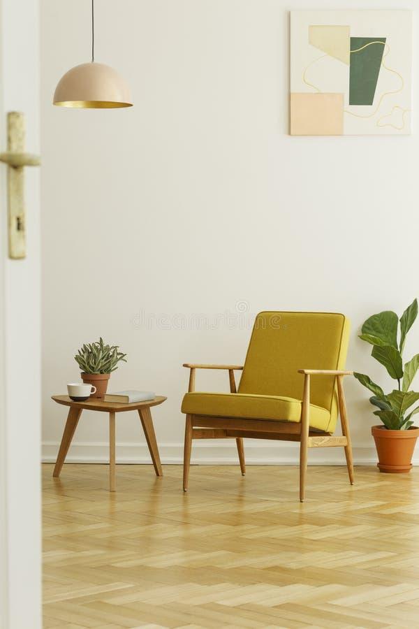 Butaca y mesa de centro amarillas con una taza y una planta en un herri imagen de archivo