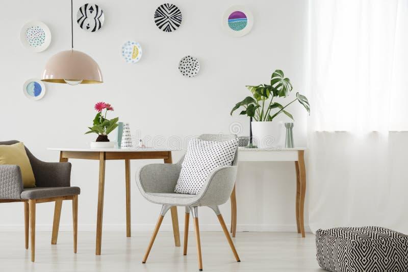 Butacas retras, tabla, lámpara, decoración de cerámica de la pared y fotografía de archivo libre de regalías