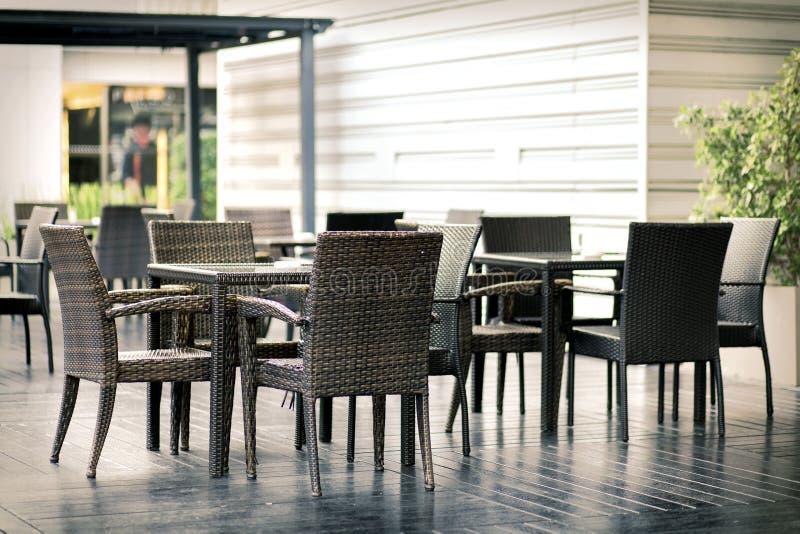 Butacas y tabla al aire libre de la rota de los muebles en terraza imagen de archivo