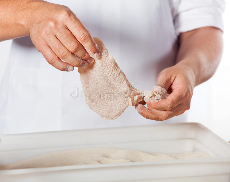 Butcher Adding Flour To Chicken Meat stock images
