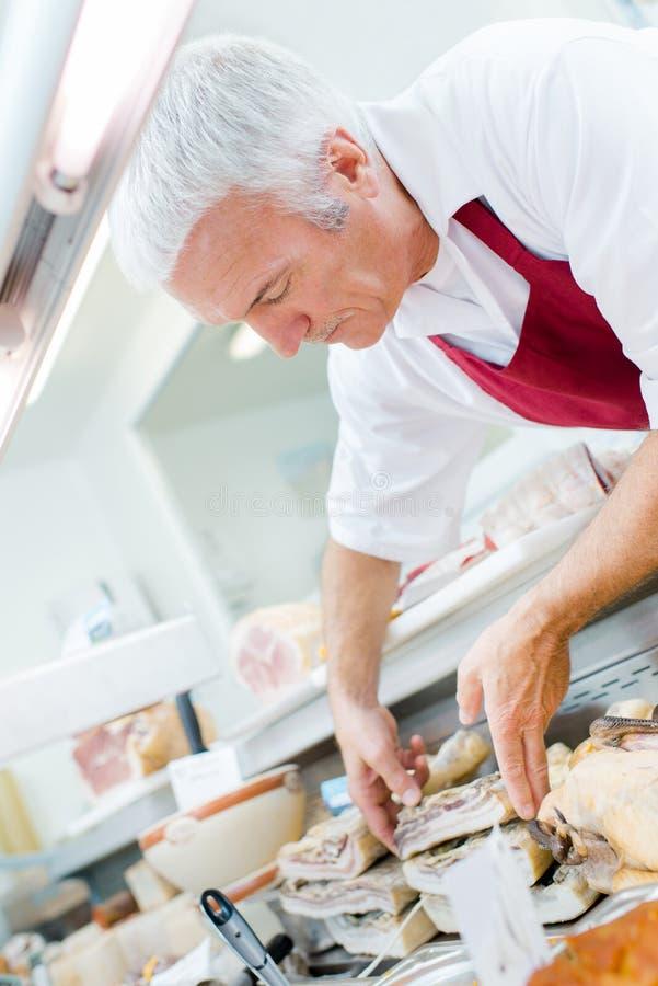 Butcher arranging shop display stock photography