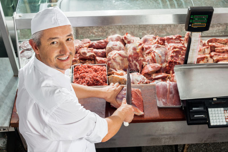 Butcher Cutting Meat At Display Cabinet. High angle portrait of butcher cutting meat at display cabinet in butchery stock images