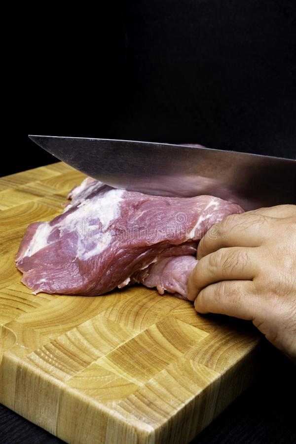 Butcher cutting pork on kitchen on wooden board on black background royalty free stock image