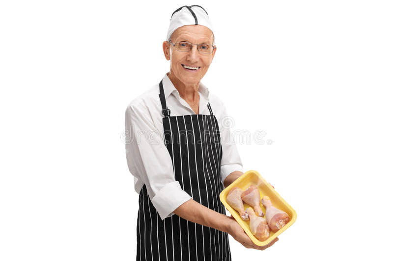 Butcher holding a pack of chicken drums. Elderly butcher holding a pack of chicken drums isolated on white background royalty free stock photography