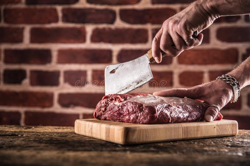 Butcher man hands cutting raw beef steak in butchery royalty free stock photos