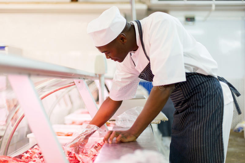 Butcher picking pieces meat stock photo