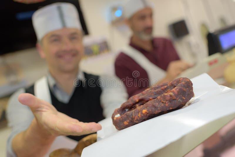 Butcher presenting chorizo sausage to customer stock photo