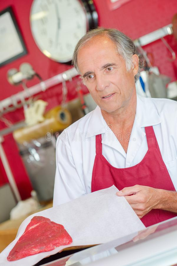 Butcher presenting cut beef to customer royalty free stock images