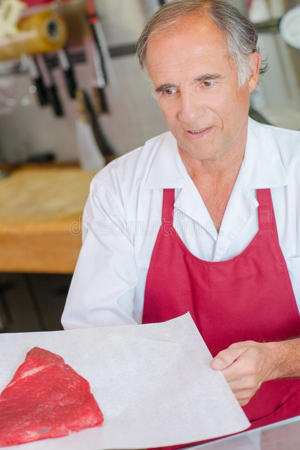 Butcher presenting cut beef to customer stock image