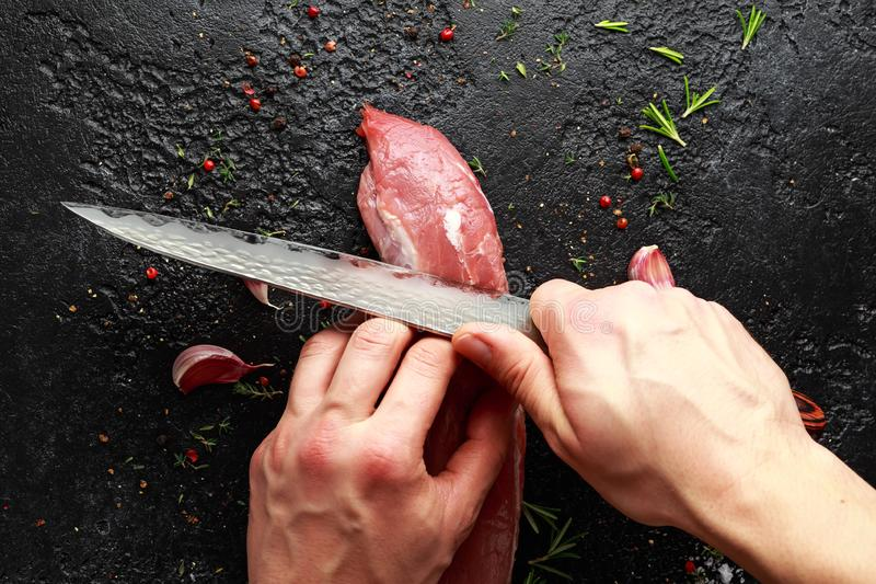 Butcher`s hands ready to cut with a knife raw pork tenderloin fillet royalty free stock photos