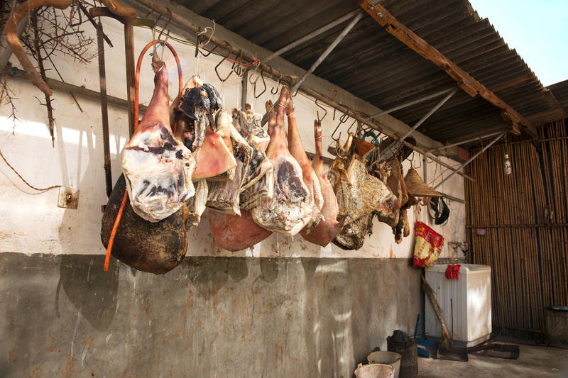 Butchered pig legs hanging on a hook and dried against a wall. Butchered pig legs hanging on a hook and dried against a wall in china royalty free stock photo