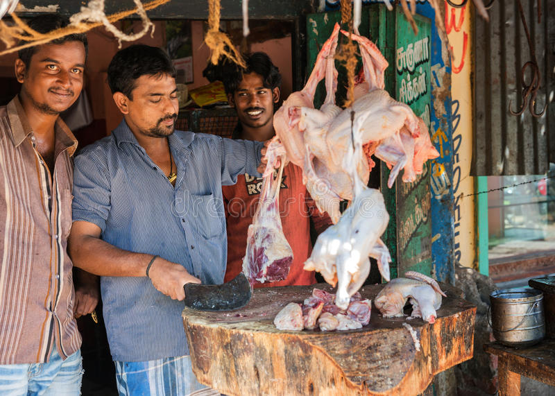 Butchers in Vellore perfoming their trades. VELLORE, INDIA - CIRCA OCTOBER 2013: Butchers cutting mutton on a wooden block in front of their shop stock image