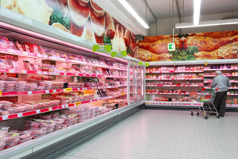 Butchery department of Supermarket. MEPPEN, GERMANY - MARCH 2016: Shopper selecting packaged meat in refrigerated section of a Kaufland hypermarket, a German