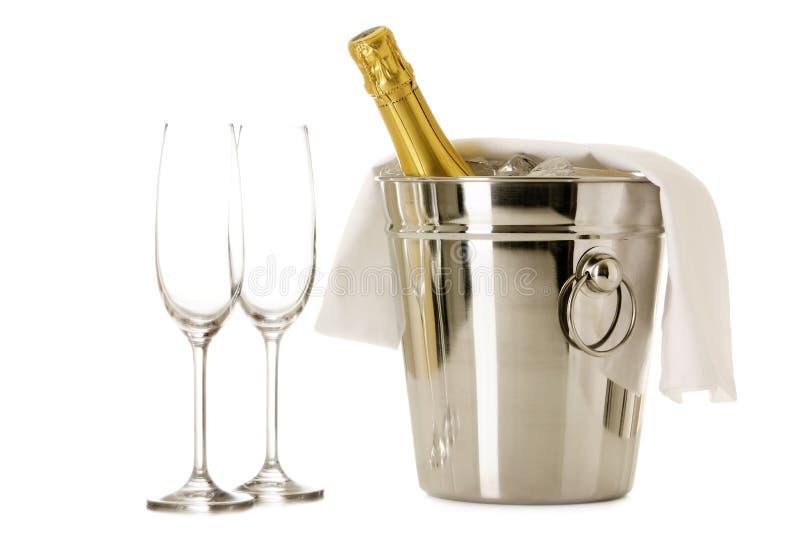 Buteljera av champagne i kylare med två exponeringsglas royaltyfria bilder