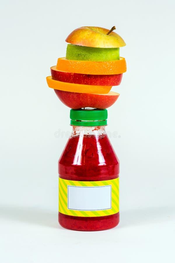 Buteljera den röda smoothien med ny frukt för stycken på vit bakgrund royaltyfri fotografi