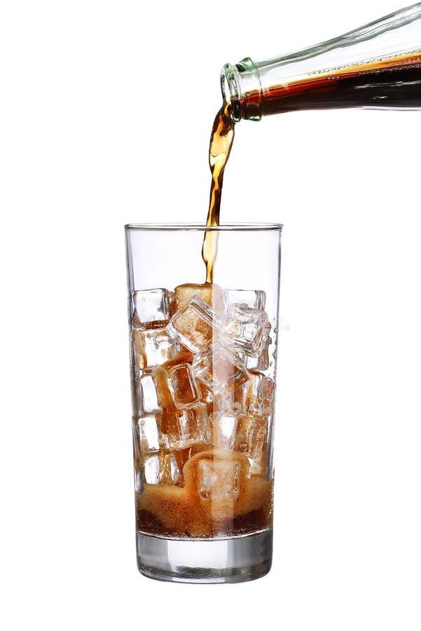 Buteljera hällande cola i drinkexponeringsglas med isolerade iskuber arkivfoton