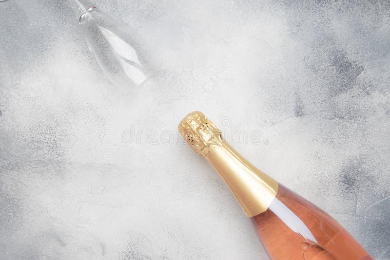 Buteljera med rosa mousserande vin eller steg champagne och exponeringsglas, grå bakgrund med stället för text-, ferie- eller dat royaltyfria foton