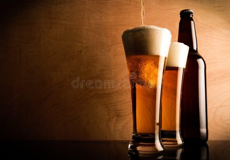 Buteljera och exponeringsglas med öl royaltyfri foto