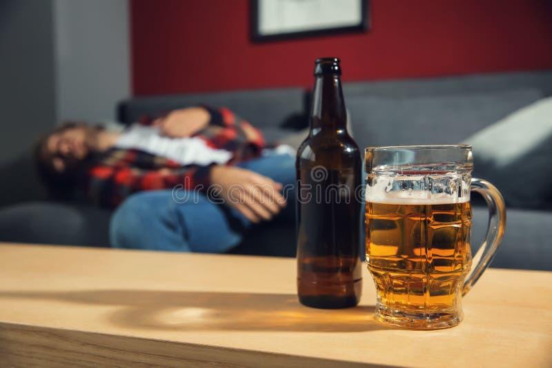 Buteljera och råna av öl på tabellen och den suddiga berusade mannen som hemma sover på soffan Tom ?lflaska mot den gamla tegelst arkivfoto
