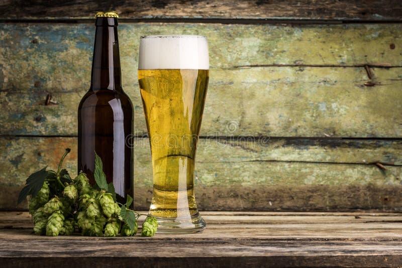 Buteljera och råna mycket av öl med gruppen av flygturer på wood bakgrund arkivfoton