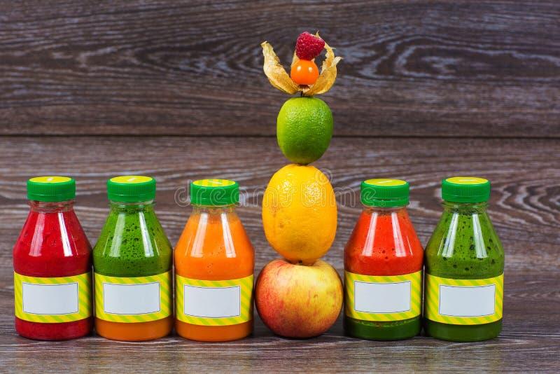Buteljerar smoothien med det nya äpplet, citronen, limefrukt, physalisen, hallon arkivbilder