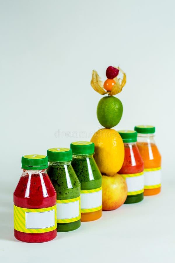 Buteljerar smoothien med det nya äpplet, citronen, limefrukt, physalisen, hallon arkivfoton