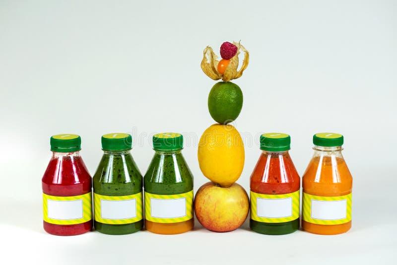 Buteljerar smoothien med det nya äpplet, citronen, limefrukt, physalisen, hallon royaltyfri bild