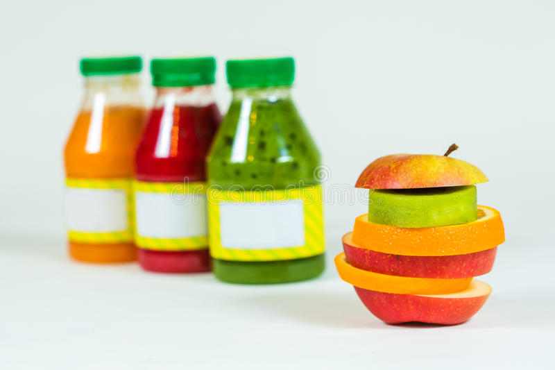 Buteljerar smoothien med ny frukt för stycken på vit bakgrund fotografering för bildbyråer