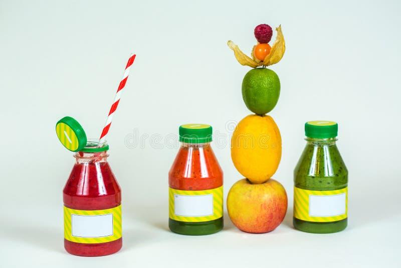 Buteljerar smoothien med sugrör, det nya äpplet, citronen, limefrukt, physalisen, hallon royaltyfria foton