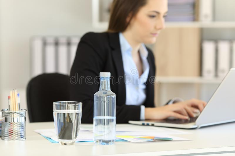 Buteljerat vatten i en kontorsarbetsplats royaltyfri foto