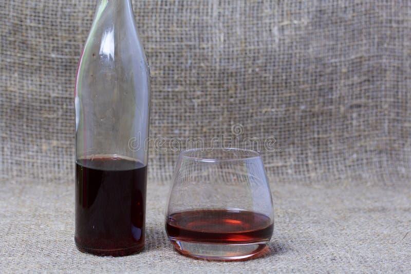 butelk? czerwonego wina Od przejrzystego szkła, zaokrąglający kształt Blisko szkła z napojem nalewającym Przeciw tłu prostacki zdjęcia stock