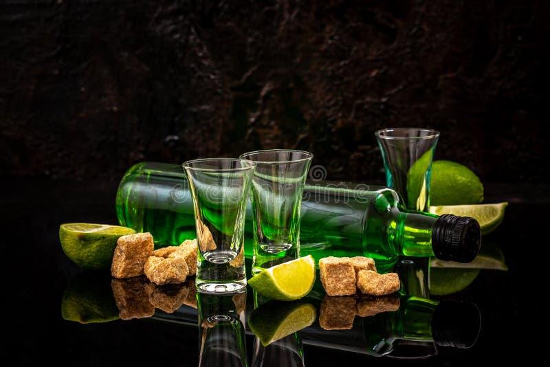 Butelka absynt i szkła z płonącym sześcianem brązowić cukier na ciemnym tle Uwalnia przestrzeń dla teksta pojęcie elity alkohol fotografia royalty free