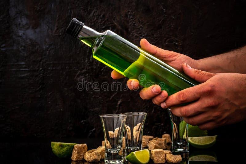 Butelka absynt w rękach barman wapno plasterki, sześcianu brązu cukier na ciemnym tle Uwalnia przestrzeń dla teksta przeciw jako  zdjęcia royalty free