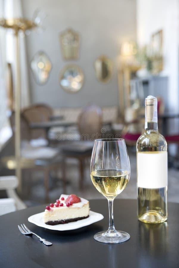 Butelka biały wino, szkło i tort na tle rocznik kawiarnia, zdjęcia royalty free