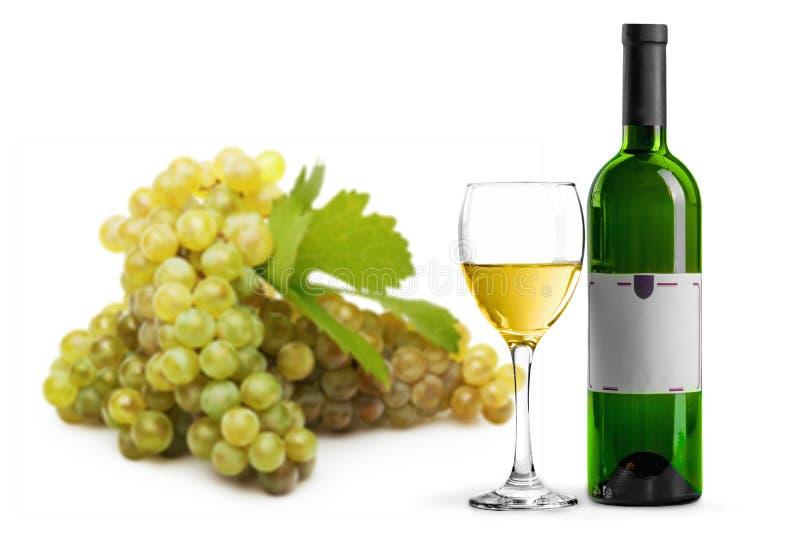 Butelka biały wino, szkło i winogrona na bielu, zdjęcia royalty free