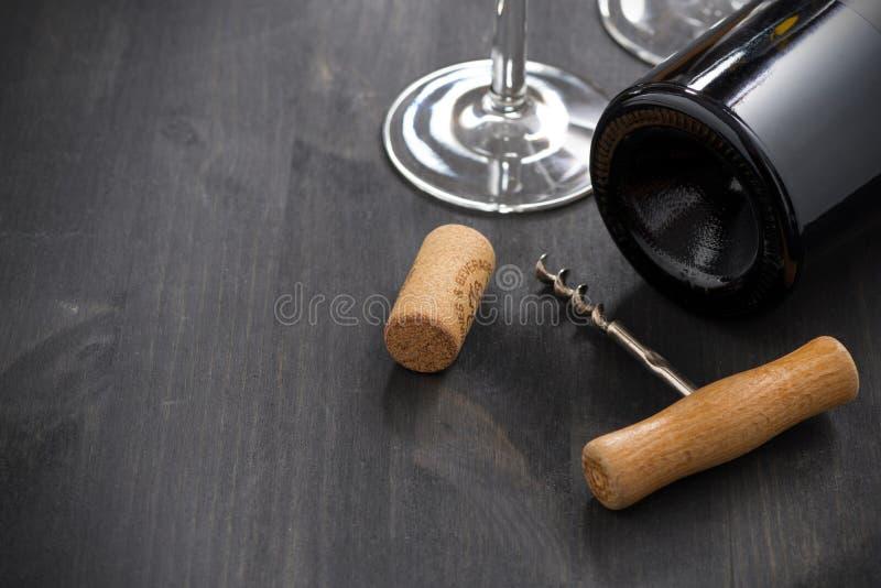 Butelka czerwone wino, corkscrew i pusty szkło, zdjęcie stock
