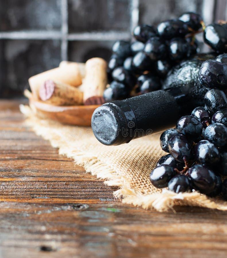 Butelka czerwone wino z świeżym winogronem i wiązka korki na drewnianym stole fotografia stock