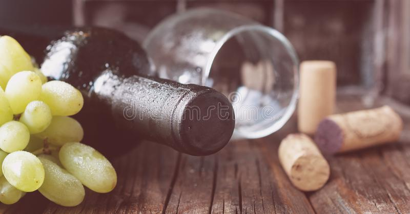 Butelka czerwone wino z świeżym winogronem i wiązka korki na drewnianym stole obraz stock