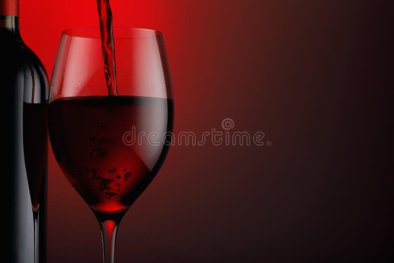 Butelka czerwone wino z szkłem na czarnym tle zdjęcia royalty free