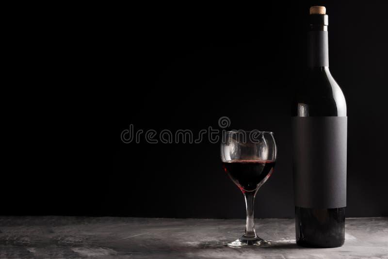 Butelka czerwony drogi wino z czarną pustą etykietką na ciemnym tle z szkłem czerwone wino Wino butelki mockup z obrazy royalty free
