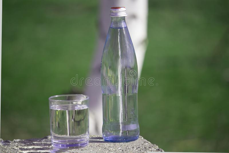 Butelka i szkło z świeżą wodą na trawy tle obrazy stock