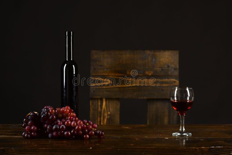 Butelka i szkło wino na brown tle Merlot, bordowie lub Cabernet wina skład, Set ciemni winogrona zdjęcie stock