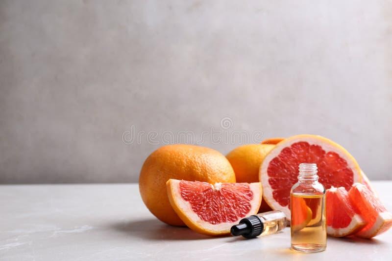 Butelka istotny olej i grapefruits na popielatym stole zdjęcia stock