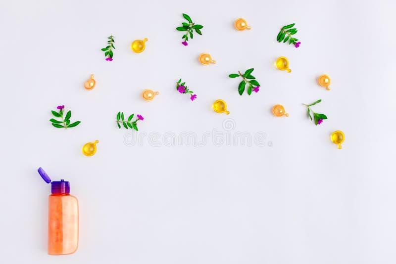 Butelka istotny olej z łąką kwitnie na białym tle Mieszkanie nieatutowy, odgórny widok, naturalny obrazy royalty free