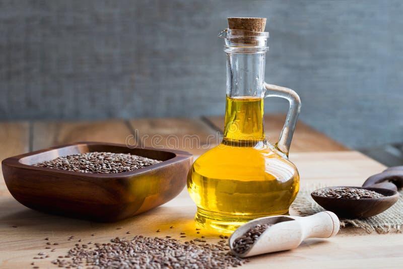 Butelka lna nasieniodajny olej z lnów ziarnami w przedpolu, zdjęcie stock