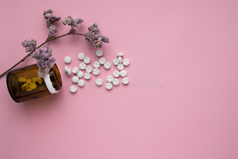 Butelka medycyny i rozrzucone pigułki na pastelowych menchii tle Rozdzierać witaminy na jaskrawym tle leczniczy ziele obraz royalty free